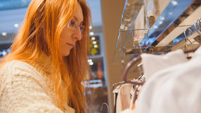 Портрет женщина в стеклах на магазине одежды выбрал платье - концепцию покупок Стоковая Фотография