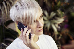 Портрет женщины битника кавказской с белокурыми короткими волосами говоря мобильным телефоном Усмехаясь сторона полу-стороны, кры стоковая фотография