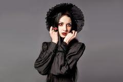 Портрет женщины брюнет в черном платье и классическом готическом хлеве Стоковая Фотография