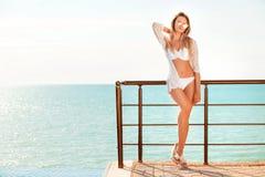 Портрет женщины в белом костюме заплыва представляя на пляже Стоковая Фотография