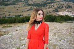 Портрет женщины в длинном платье шарлаха в лесе в горах Стоковые Фото