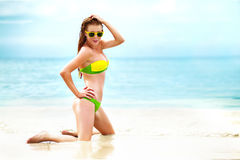 Портрет женщины в желтом заплыве представляя на тропическом пляже стоковые фотографии rf