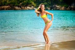 Портрет женщины в желтом заплыве представляя на тропическом пляже Стоковая Фотография