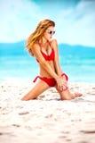 Портрет женщины в красном заплыве представляя на тропическом пляже стоковое фото rf