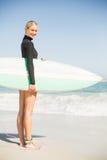 Портрет женщины в мокрой одежде держа surfboard на пляже Стоковая Фотография RF
