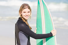 Портрет женщины в мокрой одежде держа surfboard на пляже Стоковая Фотография