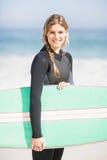 Портрет женщины в мокрой одежде держа surfboard на пляже Стоковые Фото