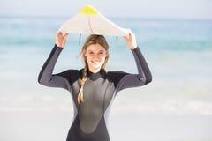 Портрет женщины в накладных расходах нося surfboard мокрой одежды Стоковые Фотографии RF