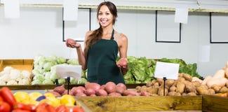 Портрет женщины в рисберме продавая органические картошки в магазине Стоковая Фотография RF