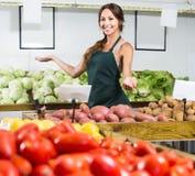 Портрет женщины в рисберме продавая органические картошки в магазине Стоковые Фотографии RF