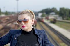 Портрет женщины в солнечных очках против железнодорожных путей Стоковые Фото