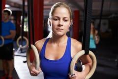 Портрет женщины в спортзале работая с гимнастическими кольцами Стоковые Фото