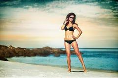 Портрет женщины в черном заплыве представляя на тропическом пляже стоковая фотография
