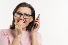 Портрет женщины говорит секреты и сплетню на сотовом телефоне Белизна предпосылки, студия, космос экземпляра Стоковые Изображения RF