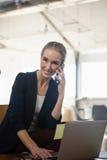 Портрет женщины говоря на телефоне пока использующ компьтер-книжку в офисе Стоковые Изображения