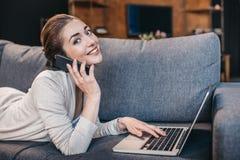 Портрет женщины говоря на smartphone и используя компьтер-книжку дома Стоковые Изображения