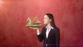 Портрет женщины держа деревенский деревянный дом на открытой ладони руки, над изолированной предпосылкой студии владение домашнег Стоковое фото RF