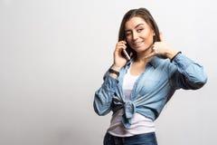 Портрет женщины детенышей усмехаясь счастливой говоря на мобильном телефоне и показывая вызывает меня Образ жизни, люди и концепц Стоковые Фото