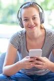 Портрет женщины дома течь музыка от мобильного телефона к беспроводным наушникам стоковое фото