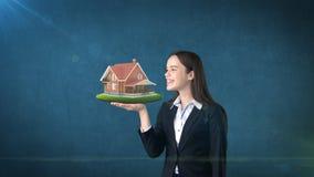 Портрет женщины держа деревенский деревянный дом на открытой ладони руки, над изолированной предпосылкой студии владение домашнег Стоковые Фото