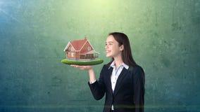 Портрет женщины держа деревенский деревянный дом на открытой ладони руки, над изолированной предпосылкой студии владение домашнег Стоковое Фото