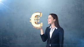 Портрет женщины держа золотой знак евро на открытой ладони руки, над изолированной предпосылкой студии владение домашнего ключа п Стоковое фото RF