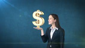 Портрет женщины держа золотой знак доллара на открытой ладони руки, над изолированной предпосылкой студии владение домашнего ключ Стоковые Фото