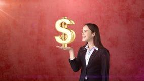 Портрет женщины держа золотой знак доллара на открытой ладони руки, над изолированной предпосылкой студии владение домашнего ключ Стоковые Изображения