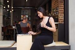 Портрет женщины детенышей довольно латинской работая на ее портативном компьютере пока ослабляющ в современном кафе во время пере Стоковые Фото