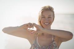 Портрет женщины делая форму сердца с руками на пляже Стоковое Изображение RF