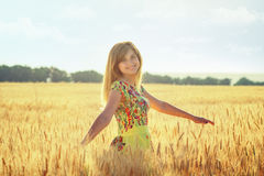 Портрет женщины завихряясь на ушах пшеницы field на заходе солнца Стоковое Изображение