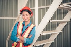 Портрет женщины инженера представляя пересеченные оружия уверенно и стоковая фотография