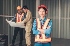 Портрет женщины инженера стоит перед другим методом стоковое изображение rf