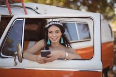 Портрет женщины используя мобильный телефон пока полагающся на двери Стоковые Изображения