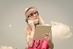 Портрет женщины используя цифровую таблетку с ретро телефонной трубкой вне Стоковое фото RF