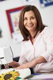 Портрет женщины используя электрическую швейную машину Стоковые Фотографии RF