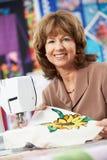 Портрет женщины используя электрическую швейную машину Стоковые Фото