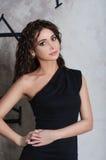 Портрет женщины красоты модельный с курчавое коричнев-с волосами в черном dre Стоковая Фотография