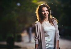 Портрет женщины красоты с совершенной улыбкой идя на улицу и смотря камеру, свет захода солнца Стоковое Изображение RF