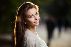 Портрет женщины красоты с совершенной улыбкой идя на улицу и смотря камеру, свет захода солнца Стоковое Изображение