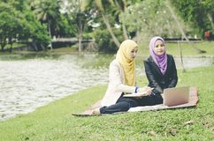 Портрет женщины молодого симпатичного приятного смешивания этнической сидя на траве на парке зеленого цвета лета и имея обсуждени Стоковые Изображения
