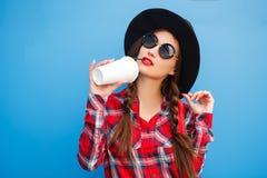 Портрет женщины моды красоты усмехаясь с кофе в солнечных очках на голубой предпосылке напольно Copyspace Стоковые Фото