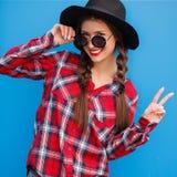 Портрет женщины моды красоты усмехаясь с кофе, делая мир пальцами в солнечных очках на голубой предпосылке напольно Стоковое Изображение