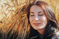 Портрет женщины на поле вполне желтых ушей Стоковое Изображение