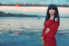 Портрет женщины на речном береге на заходе солнца Стоковое фото RF