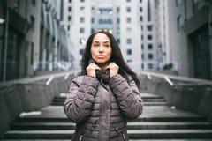 Портрет женщины на теме дела Молодое кавказское брюнет с длинной девушкой волос в длинной куртке, пальто стоит на центе дела Стоковое Фото