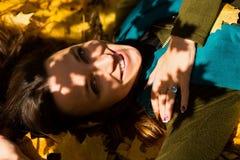 Портрет женщины осени лежа над листьями и усмехаться Стоковое Изображение