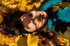 Портрет женщины осени лежа над листьями и усмехаться Стоковые Фотографии RF