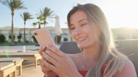 Портрет женщины отдыхая на deckchair использующ смартфон, просматривая интернет, перечени через социальные средства массовой инфо видеоматериал