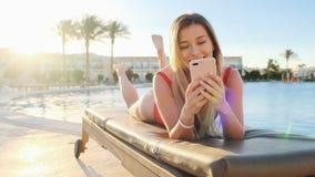 Портрет женщины отдыхая на deckchair использующ смартфон, просматривая интернет, перечени через социальные средства массовой инфо сток-видео